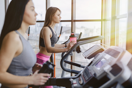 Foto per Girls in the gym are trained on treadmills and drink water, smiling and healthy - Immagine Royalty Free