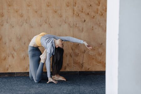 Photo pour Cozy young attractive girl doing fitness exercises with yoga on the floor on a wooden background at gym - image libre de droit