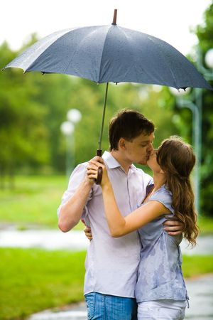 Portrait of romantic couple embracing and kissing each other under umbrella during rain