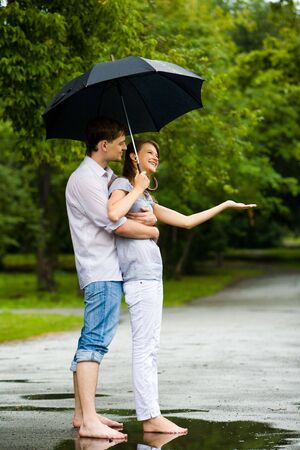 Portrait of man hugging happy woman under umbrella