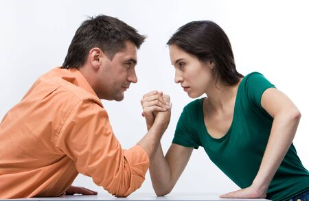 Man and woman doing arm wrestling showing their displeasure