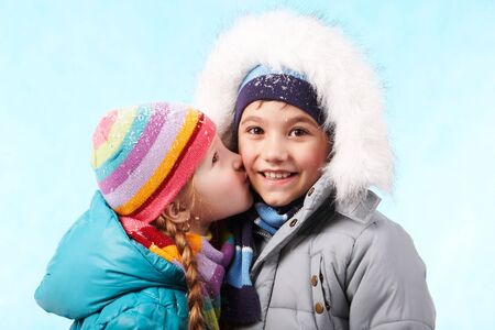 Portrait of happy child smiling at camers while being kissed by pretty girl