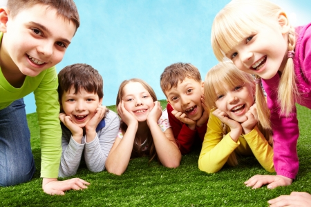 Image of playful children lying on a green grass and looking at camera