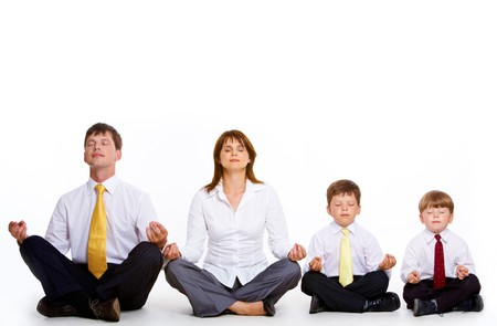 Photo of friendly family sitting in pose of lotus in a row and meditating over white background