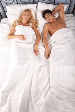 Photo of attractive woman and man sleeping in bed