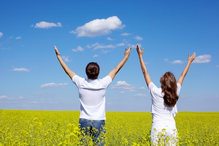 Photo pour Back view of young guy and girl praising God in yellow meadow at summer - image libre de droit