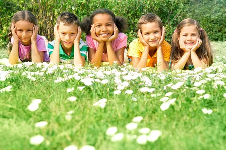 Portrait of cute kids lying on green grass and looking at camera