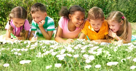 Portrait of cute kids drawing in natural environment together