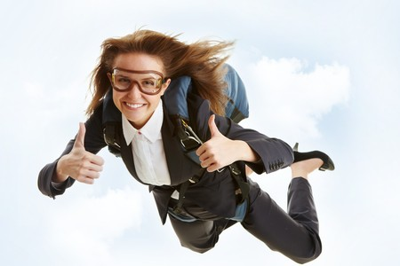 Conceptual image of young female flying with parachute and showing thumbs up