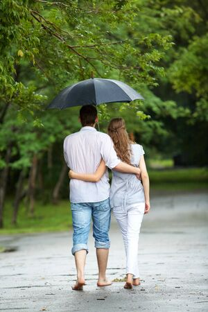 Rear view of a couple walking in the rain under umbrella and hugging