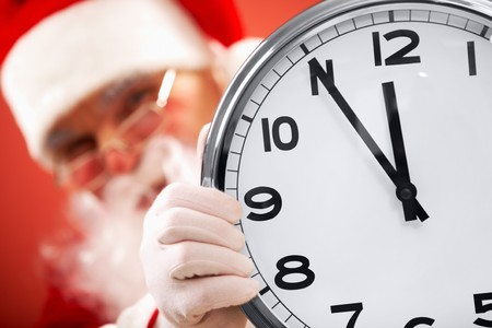 clock showing five minutes to midnight with Santa on background