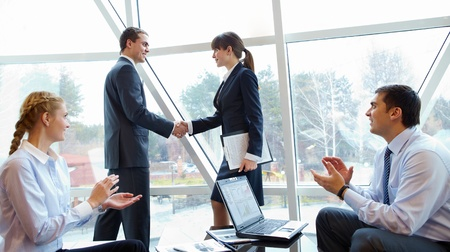 Photo of confident partners handshaking at meeting after making an agreement