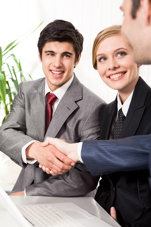 Photo of successful business partners handshaking after striking great deal with smiling woman near by