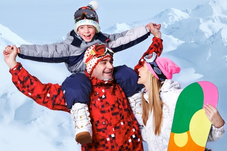 Portrait of happy family with snowboards having fun on winter resort