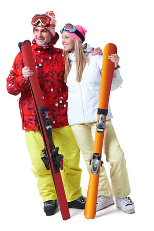 Portrait of happy couple with skis in hands looking aside with smiles