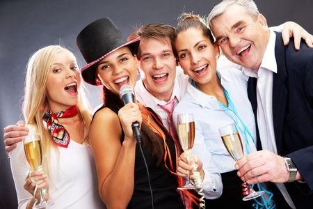 Photo of businesspeople with flutes of champagne singing at Christmas party