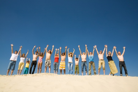 Image of many friends standing on sandy beach with their arms raised against blue sky