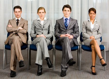 Portrait of confident business group sitting in row and looking at camera