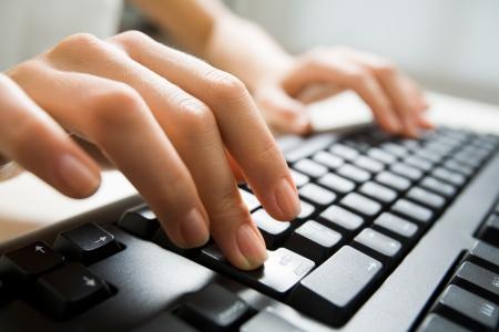 Image of female fingers pushing enter key during computer work