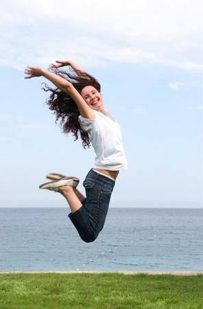 Photo pour Joyful female in high jump over green grassland with blue sea and sky at background - image libre de droit