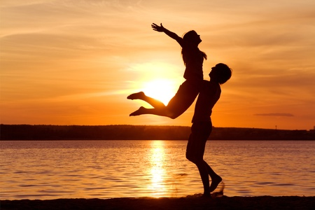 Photo for Figures of happy guy holding his girlfriend while the latter raising her arms at sunset - Royalty Free Image