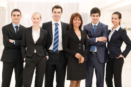 Portrait of smart business people standing next to each other and looking at camera