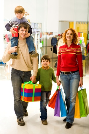 Portrait of family walking down shopping mall after buying Christmas presents