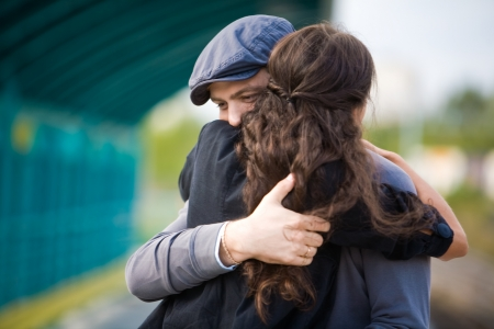 Photo of pretty girl and her boyfriend embracing during seeing off