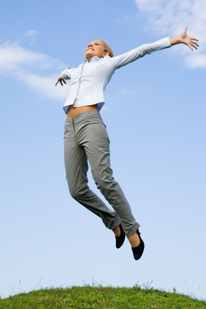 Portrait of happy female jumping over green grass against blue sky