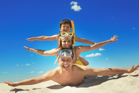 Photo pour Happy family with flippers lying on sand and looking at camera  - image libre de droit