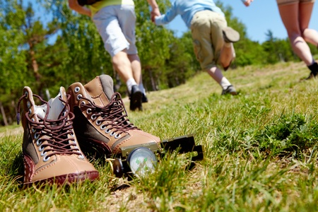 Photo pour Image of pair of boots and compass on background of people running down green grass - image libre de droit