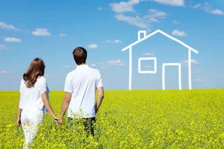 Photo for Back view of amorous couple in yellow meadow looking at drawn house - Royalty Free Image