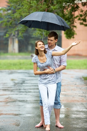 Portrait of woman and man walking under umbrella during rain