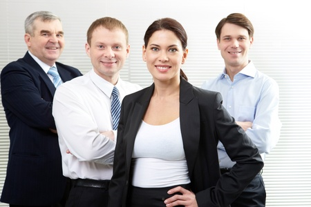A business team of four looking at camera and smiling