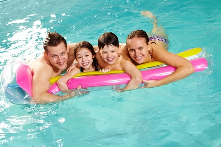 Cheerful family in swimming pool having nice time