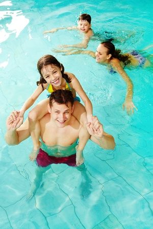 Photo of happy girl sitting on her father shoulders in pool with swimming boy and mother on background