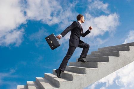 Foto de Image of confident businessman with briefcase walking upstairs - Imagen libre de derechos