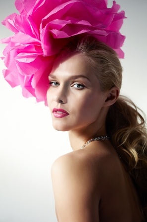 Gorgeous woman with pink flower on head looking at camera