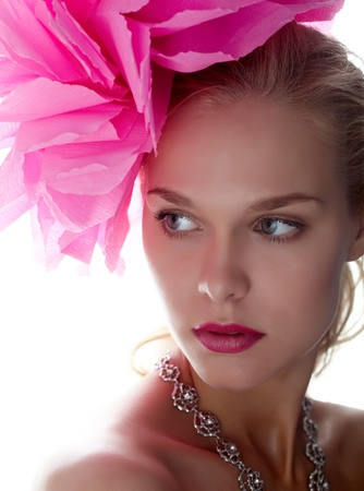 Gorgeous woman with pink flower on head looking aside