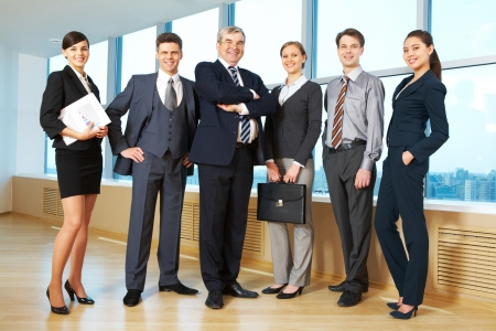Portrait of confident business group standing in row and looking at camera