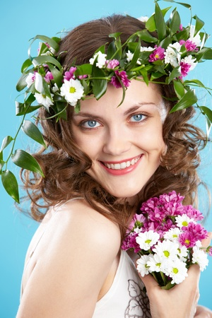Beautiful woman in floral wreath looking at camera with smile