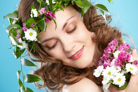Beautiful woman in floral wreath looking aside
