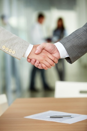 Photo of handshake of business partners after signing contract
