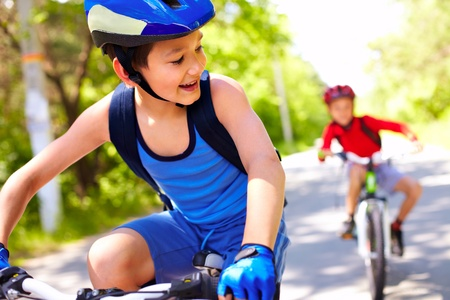 Foto per Two little boys riding bikes one after another  - Immagine Royalty Free