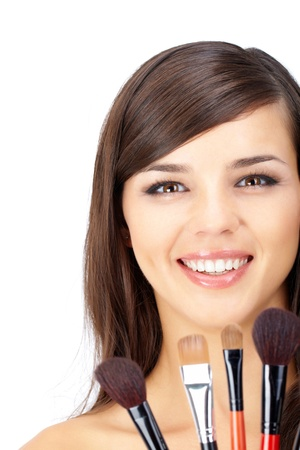 Portrait of a woman with make-up and several cosmetic brushes