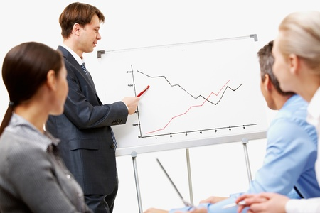 Image of confident man making presentation and pointing at graph on whiteboard