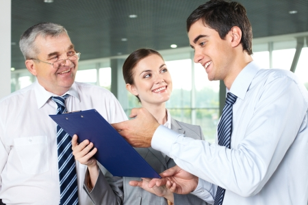 Photo pour Smiling man explaining business document while his partners looking at him - image libre de droit
