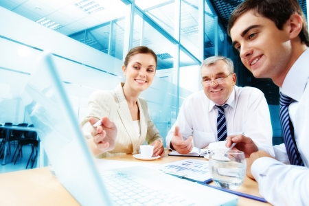 Foto de A business team of three sitting in office and planning work - Imagen libre de derechos