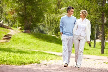 Portrait of young amorous couple walking in park in summer