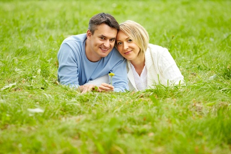 Portrait of young couple looking at camera while lying on green grass